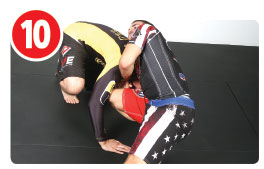 Now Garry picks a side and slides his right arm deeper under his opponent's neck while bringing his right thigh up along the head. While doing this movement, Garry's also dropping his head to his opponent's left shoulder and his left elbow is up high with his hands clasped. The trick here is not the arm position, but the rotation of Garry's body. The placement of the knee prevents the other guy's head from popping out when Garry rotates for the finish.