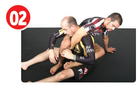 Garry wants to grab his own right knee with his right hand after the neck escape. To do this, Gary posts his left hand to the mat twisting a bit so he can feed his right knee to his right hand.